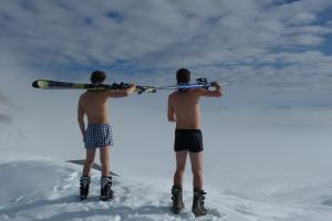 2 men wearing boxers and boots with skis on shoulder